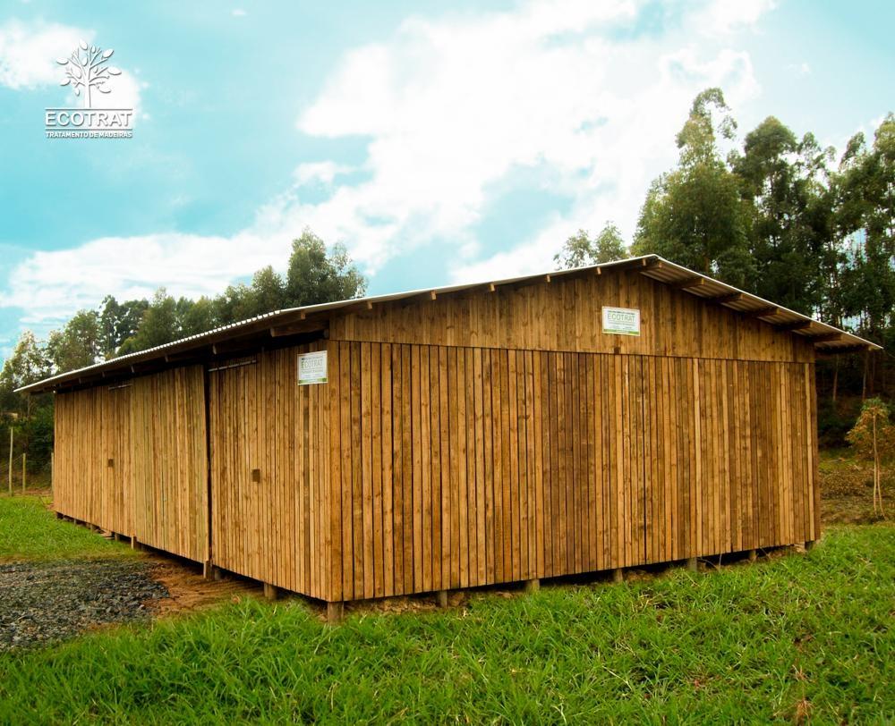Galpão com vão livre de 12m de comprimento. Para o fechamento do galpão e seus portões, foram utilizadas tábuas serradas de pinus tratado. Cobertura com telhas de aluzinco.