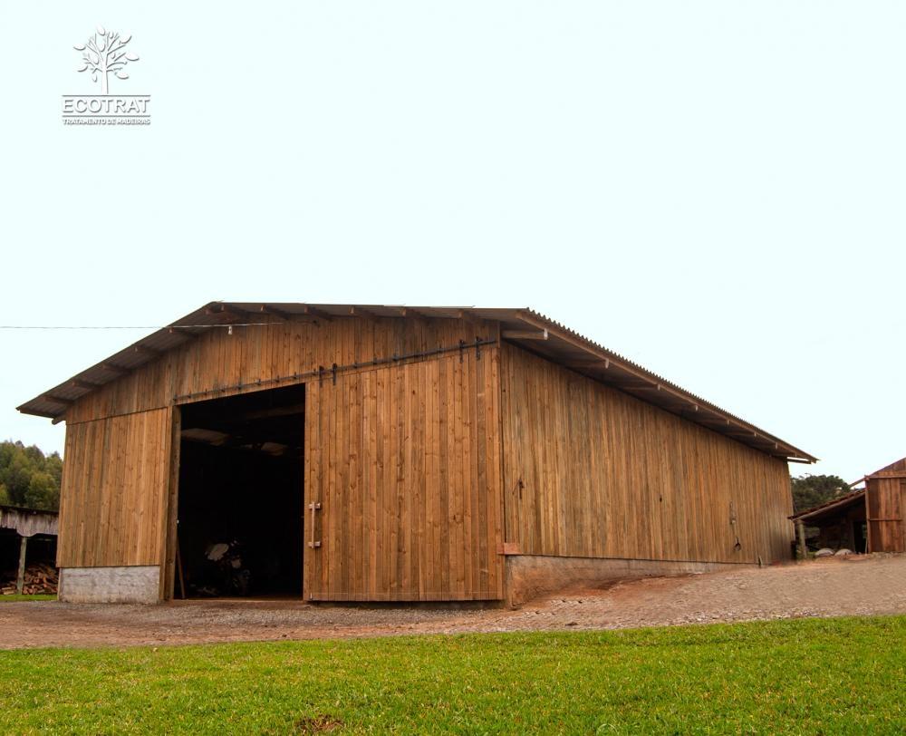 Galpão com vão livre de 15m de comprimento. Para o fechamento do galpão e seus portões, foram utilizadas tábuas serradas de pinus tratado. Cobertura com telhas de fibra de cimento.