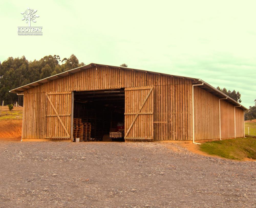 Galpão com vão livre de 15m de comprimento. Para o fechamento do galpão e seus portões, foram utilizadas tábuas serradas de pinus tratado. Cobertura com telhas de fibro cimento.