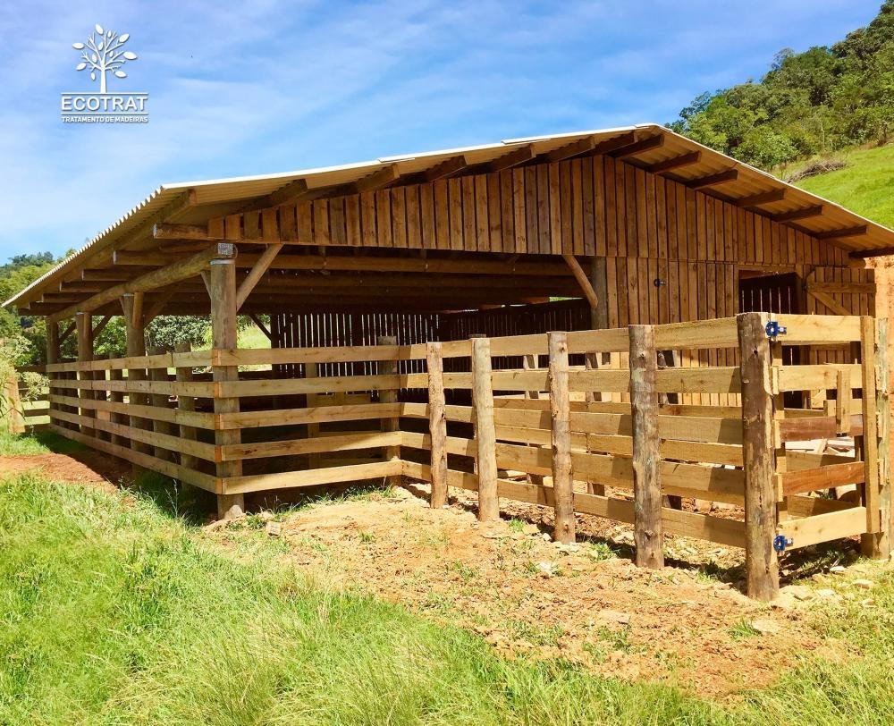 Galpão com vão livre de 12m de comprimento para confinamento de animais. Para o fechamento do galpão e seus portões, foram utilizadas tábuas serradas de pinus tratado. Cobertura com telhas de fibra de cimento.
